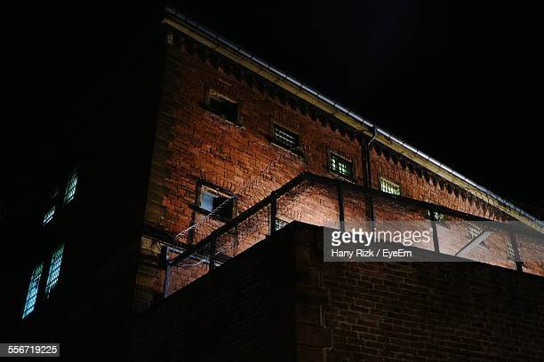 low angle view of prison against clear sky at night - prison building stock pictures, royalty-free photos & images