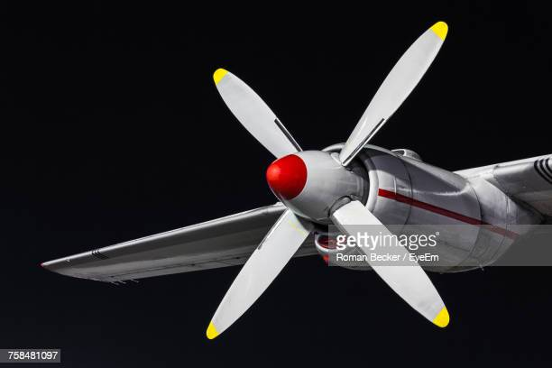 Low Angle View Of Propeller Airplane Against Black Background