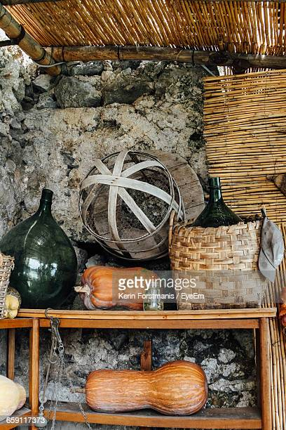 Low Angle View Of Pumpkins With Bottle And Baskets On Table