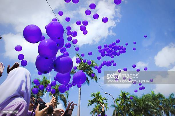 Low Angle View Of Purple Balloons Hanging Against Sky