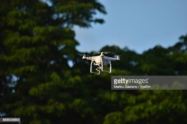 Low Angle View Of Quadcopter Flying By Trees Against Clear Sky