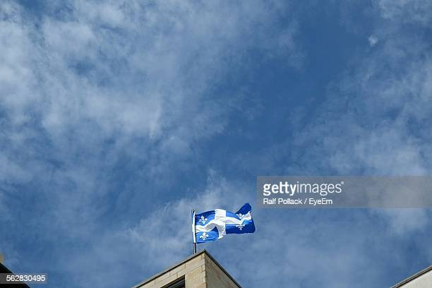 Low Angle View Of Quebec Flag Against Cloudy Sky
