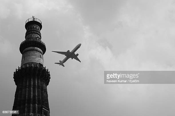 Low Angle View Of Qutub Minar Against Airplane Flying In Sky