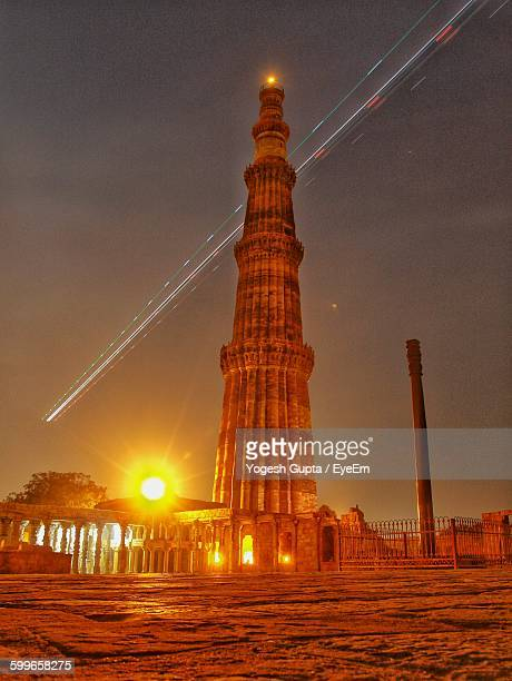 low angle view of qutub minar against sky during sunset - haryana stock photos and pictures