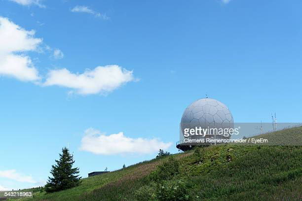 Low Angle View Of Radar Tower And Grassy Hill Against Blue Sky