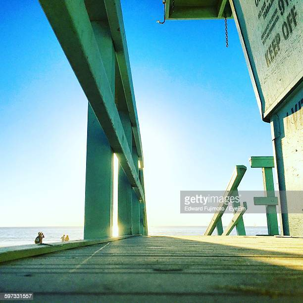Low Angle View Of Railing On Pier At Sea Against Sky During Sunset