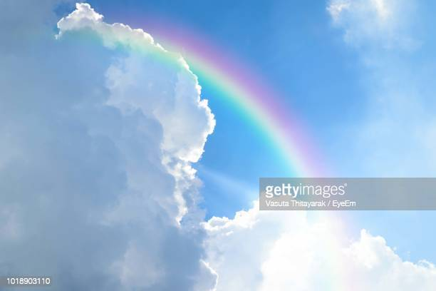 low angle view of rainbow against blue sky - rainbow stock pictures, royalty-free photos & images