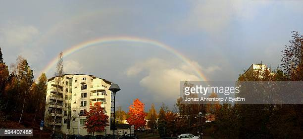 Low Angle View Of Rainbow By Buildings And Trees Against Sky