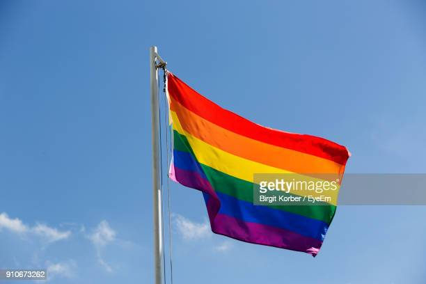 low angle view of rainbow flag against blue sky - pride flag stock pictures, royalty-free photos & images