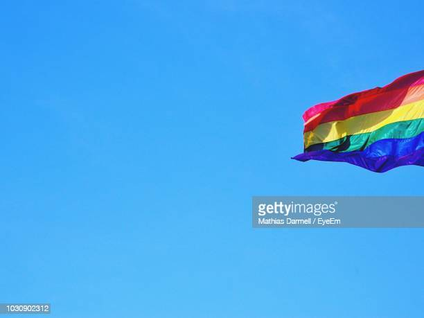 Low Angle View Of Rainbow Flag Against Clear Blue Sky