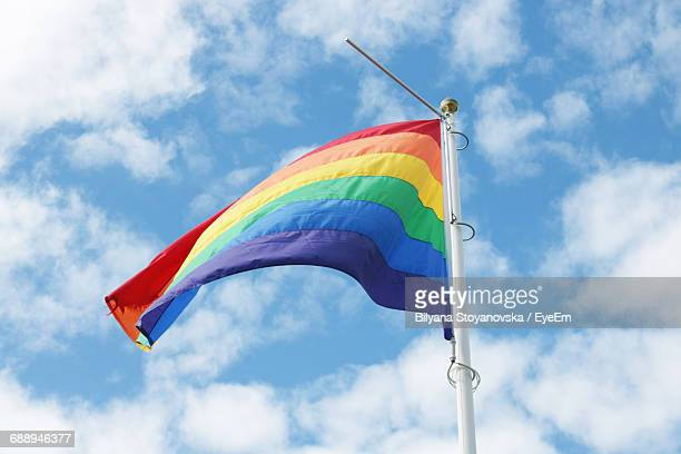 Low Angle View Of Rainbow Flag Against Cloudy Sky