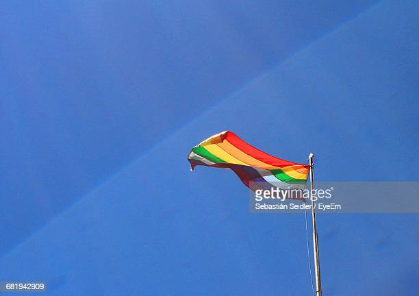 Low Angle View Of Rainbow Flag Waving Against Blue Sky