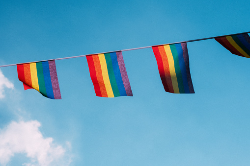 Low Angle View Of Rainbow Flags Against Sky - gettyimageskorea