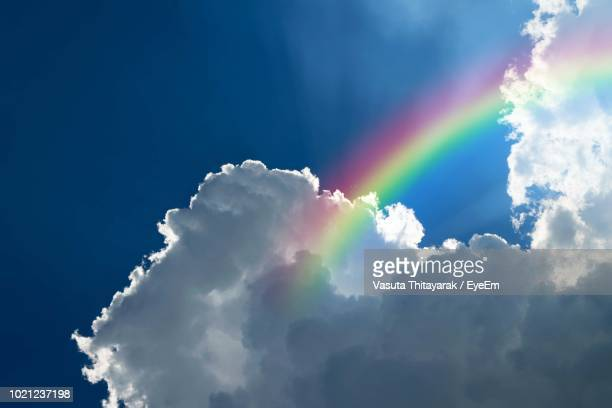 low angle view of rainbow in sky - rainbow sky stock pictures, royalty-free photos & images