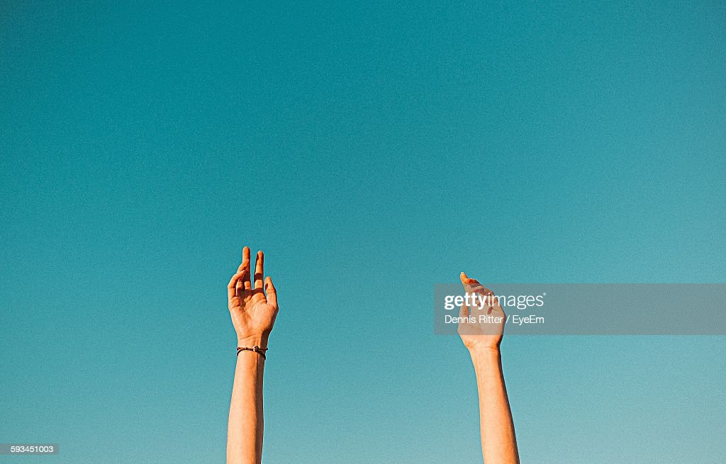 Low Angle View Of Raised Hands Against Clear Sky : Stock Photo