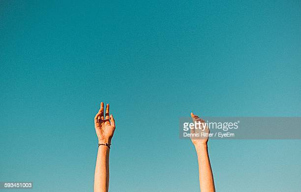 Low Angle View Of Raised Hands Against Clear Sky