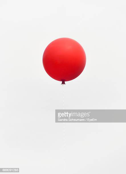 Low Angle View Of Red Balloon Flying Against Clear Sky During Party