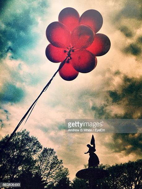 Low Angle View Of Red Balloons Against Cloudy Sky