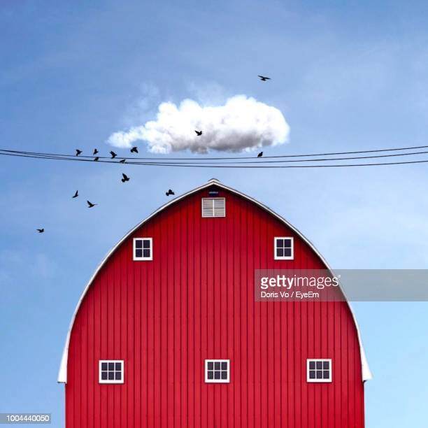 low angle view of red barn against blue sky - barn stock pictures, royalty-free photos & images