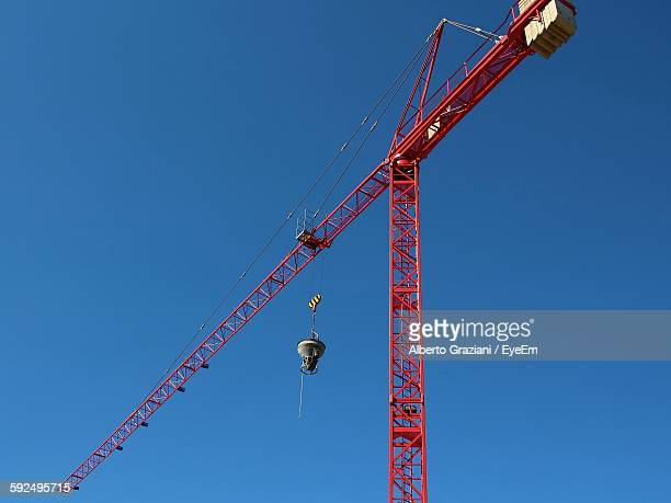 Low Angle View Of Red Crane Against Clear Blue Sky