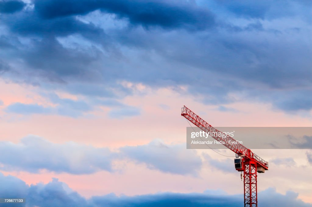 Low Angle View Of Red Crane Against Cloudy Sky : Stock Photo