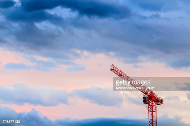 Low Angle View Of Red Crane Against Cloudy Sky