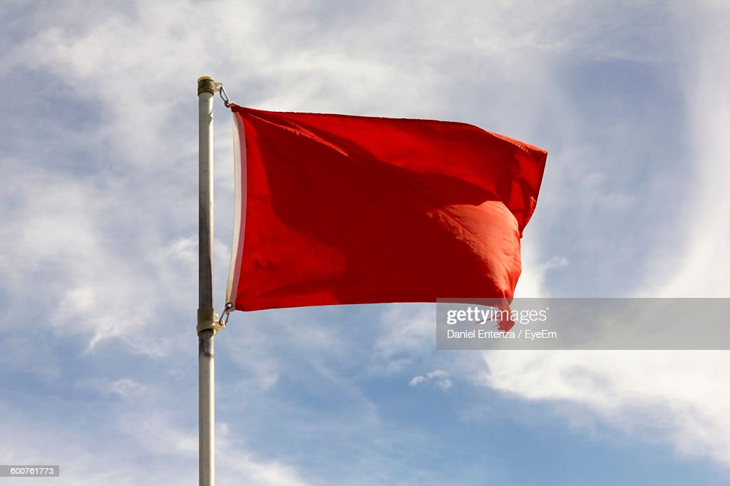 Low Angle View Of Red Flag Against Sky : Stock Photo