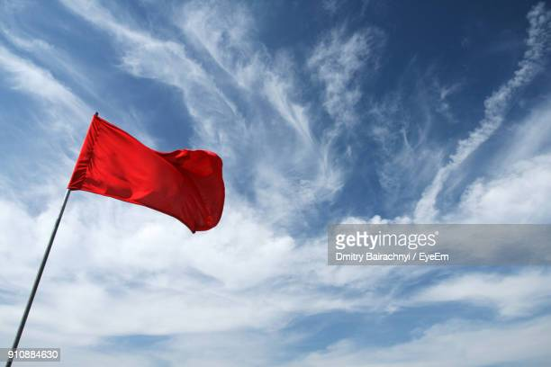 low angle view of red flag against sky - 旗 ストックフォトと画像
