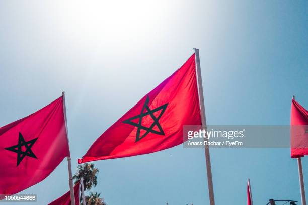 Low Angle View Of Red Flags Against Clear Blue Sky