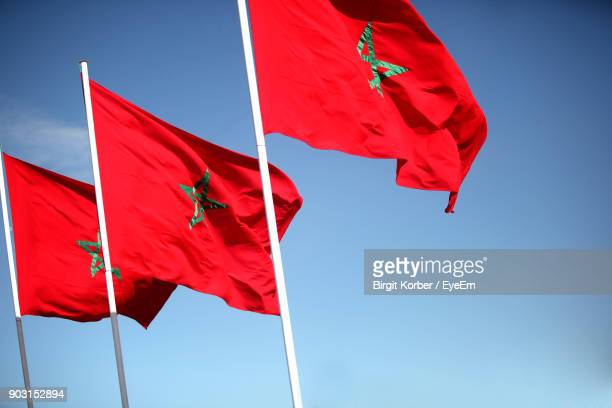 low angle view of red flags against sky - national flag stock photos and pictures