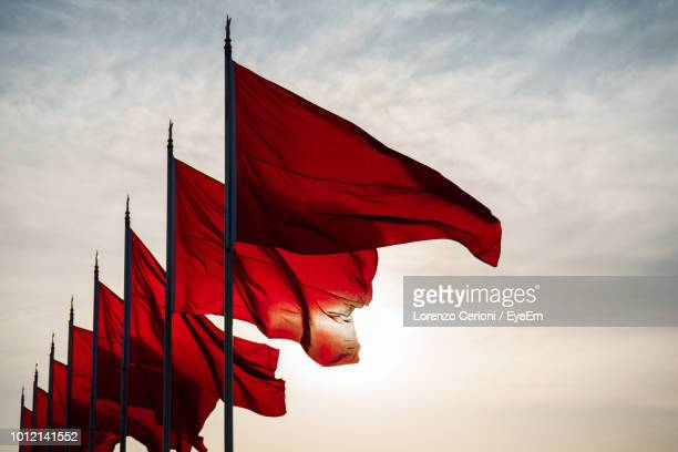 low angle view of red flags waving in row against sky during sunset - flag stock pictures, royalty-free photos & images