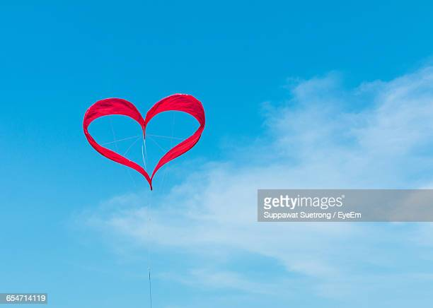 Low Angle View Of Red Heart Shape Kite Against Sky