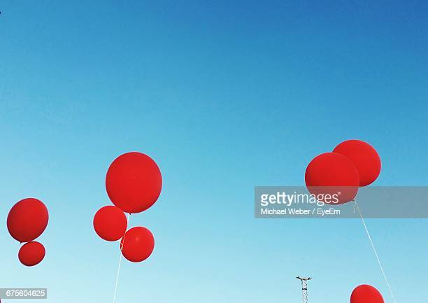 Low Angle View Of Red Helium Balloons Against Clear Sky