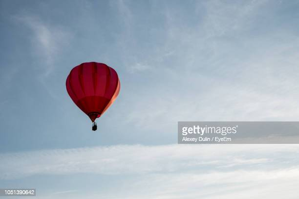 Low Angle View Of Red Hot Air Balloon Flying In Sky