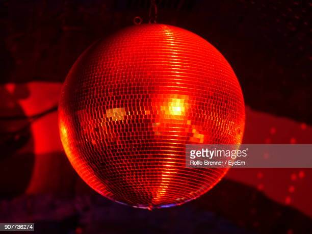 Low Angle View Of Red Illuminated Disco Ball At Night Club