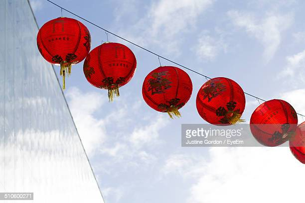 Low angle view of red lanterns hanging below the sky