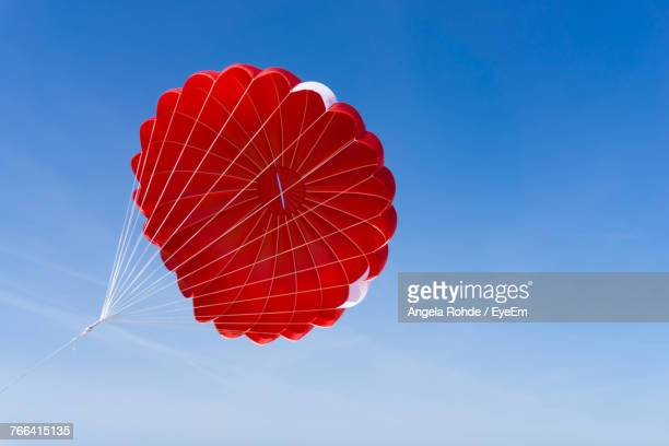 low angle view of red parachute against clear blue sky - fallschirm stock-fotos und bilder
