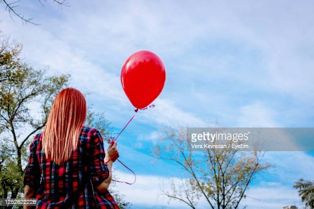 low angle view of redhead woman holding red balloon against the sky, - releasing stock pictures, royalty-free photos & images