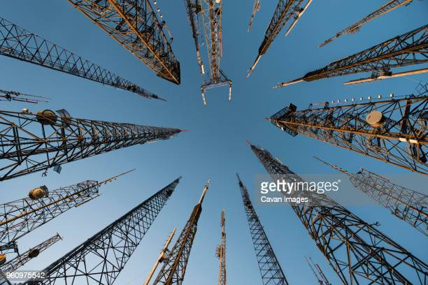 low angle view of repeater towers against clear blue sky - communications tower stock pictures, royalty-free photos & images