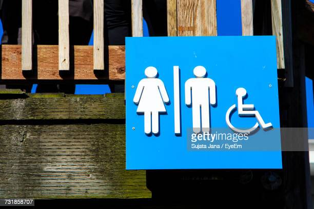 Low Angle View Of Restroom And Wheelchair Signs On Wood