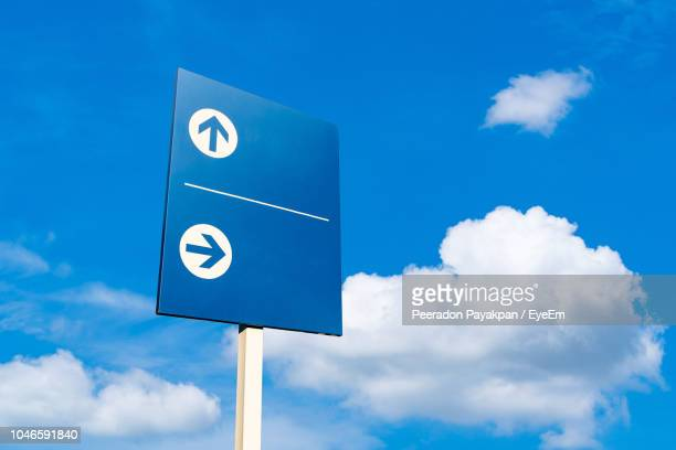 low angle view of road sign against blue sky - road sign stock pictures, royalty-free photos & images