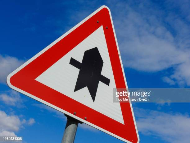 low angle view of road sign against blue sky - give way stock pictures, royalty-free photos & images