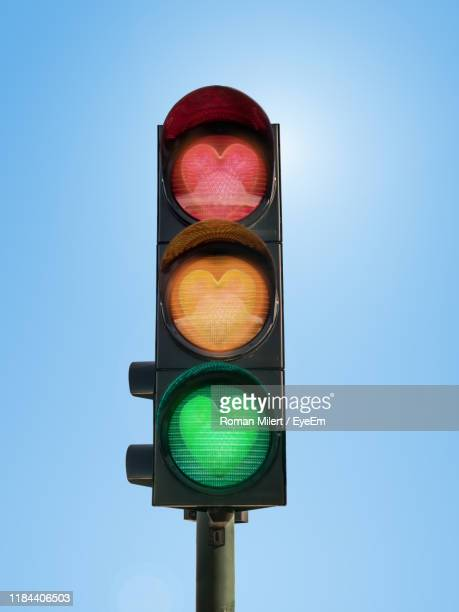 low angle view of road sign against blue sky - road signal stock pictures, royalty-free photos & images