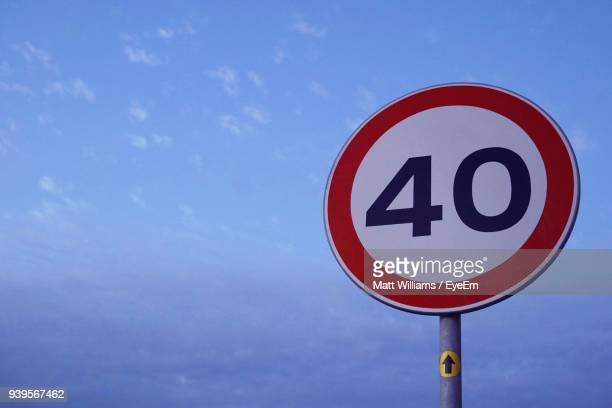 low angle view of road sign against blue sky - speed limit sign stock photos and pictures