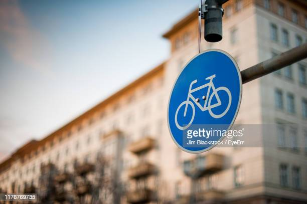 low angle view of road sign against building in city - road sign stock pictures, royalty-free photos & images