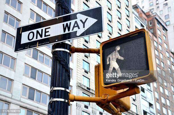 low angle view of road sign against buildings in city - one direction stock pictures, royalty-free photos & images