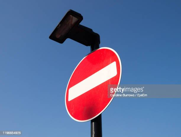 low angle view of road sign against clear blue sky - exclusion stock pictures, royalty-free photos & images