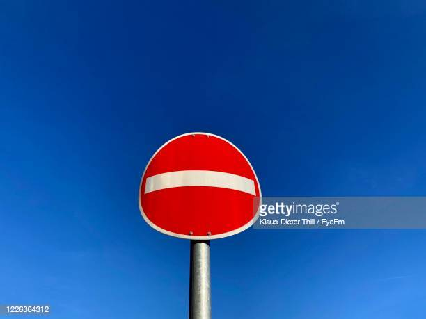 low angle view of road sign against clear blue sky - klaus-dieter thill stock-fotos und bilder