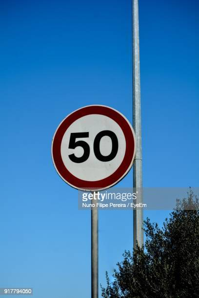 low angle view of road sign against clear blue sky - speed limit sign stock photos and pictures