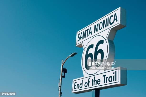low angle view of road sign against clear blue sky - santa monica stock-fotos und bilder
